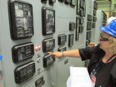 A CNSC inspector verifying a control panel