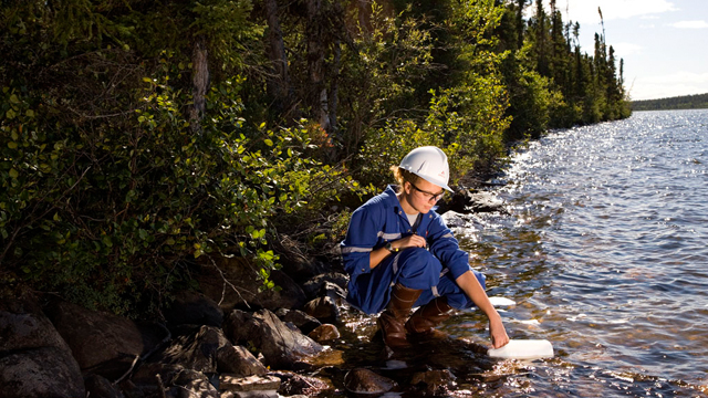 A field technician collecting a water sample from a lake downstream of a uranium mine or mill.